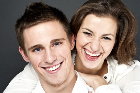 people laughing: young couple togheter on black background Stock Photo
