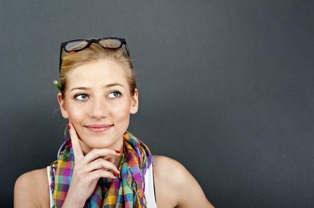 mujeres pensando: mujer joven mirar hacia arriba sobre fondo negro Foto de archivo