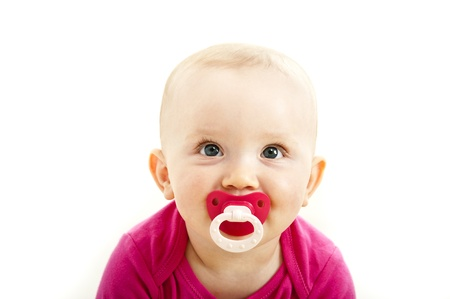 baby child with dummy in her face