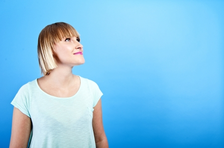 woman looking up on blue background photo