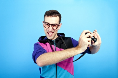 man with photocamera on blue background Stock Photo