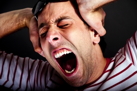 man holding head and screaming photo