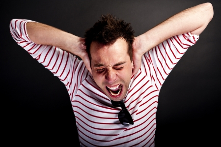 man holding head and screaming