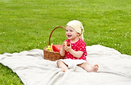 baby on blanket outdoor on grass eating a apple photo