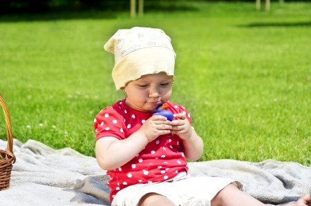 baby on green grass paying photo