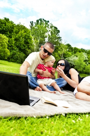 Family together on picnic time with laptop photo