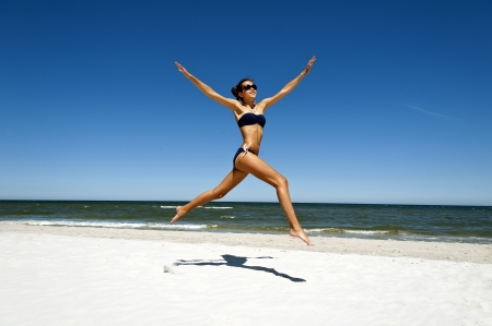 Woman jump on sand by the beach photo