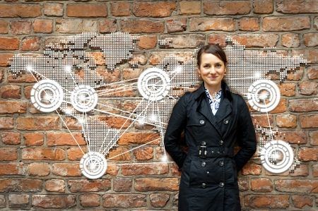 technology to communicate: Woman by the wall with world map travel Stock Photo