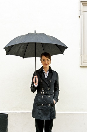 Woman under black umbrella against the white wall