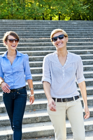 Two  beautiful woman with sunglasses on the stairs photo