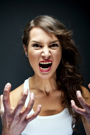 crazy woman: Angry woman on black background