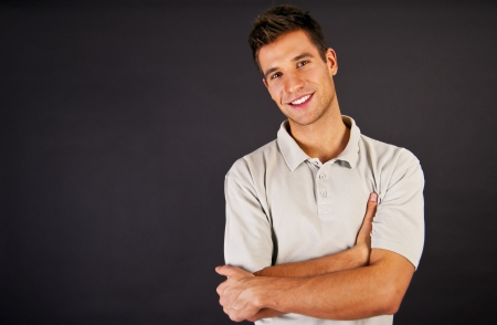 1 man: Man in grey polo t-shirt on black backgraund with smile