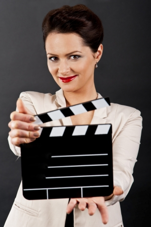 Woman with movie clap over black background photo