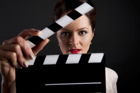 Woman with movie clap over black background Stok Fotoğraf