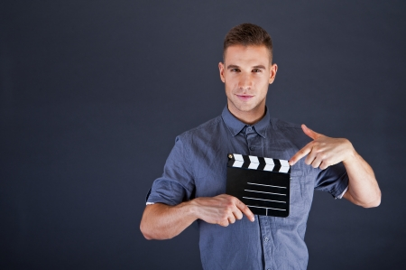 Man with movie clap over dark background photo
