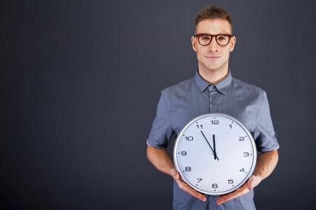 puntualidad: Hombre que sostiene el reloj de pared sobre fondo oscuro