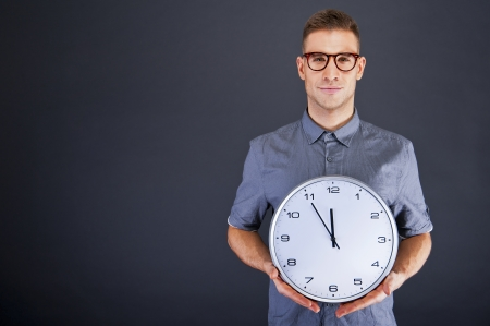 Man holding wall clock over dark background photo