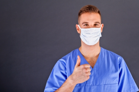 Surgeon with thumb up over dark background photo