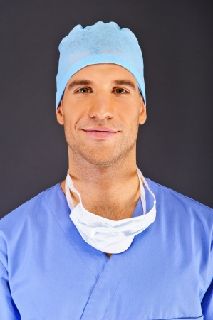 Doctor over dark background in blue shirt photo
