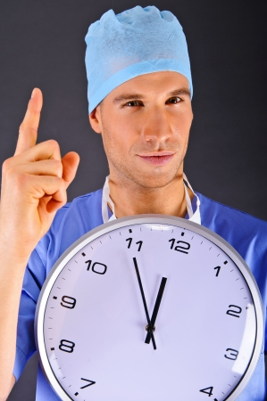 Surgeon with wall clock over dark background photo