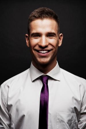 white shirt: Man with purple tie over dark background Stock Photo