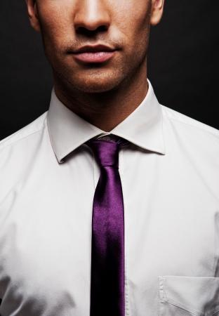 lazo negro: Hombre con corbata de color p�rpura sobre fondo oscuro