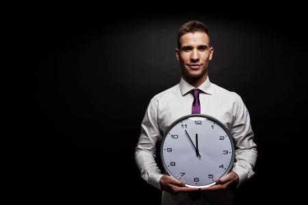 reloj de pared: Hombre con reloj de pared sobre fondo oscuro Foto de archivo