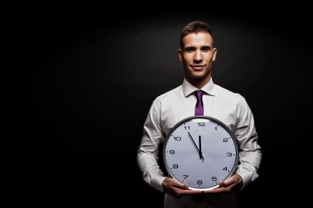 black clock hands: Man with wall clock over dark background
