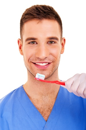 A young man brushing his teeth isolated on white background photo
