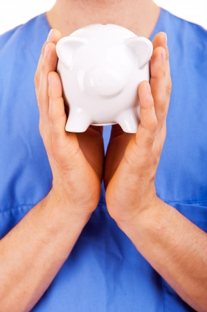 health care fees: Doctor with Caring Hands on a Piggy Bank.
