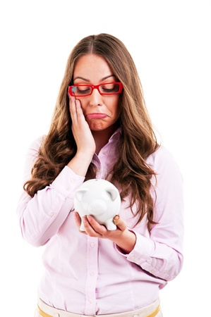 Upset woman wearing glasses holding piggy bank. Expensive eyewear glasses concept. Young female business woman isolated on white background.  photo