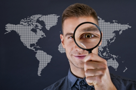 Man with magnifier and world map on dark background  photo