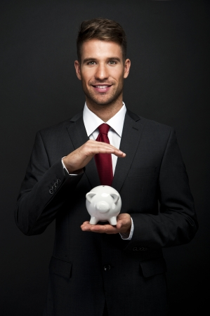 Businessman with piggy bank over dark background photo