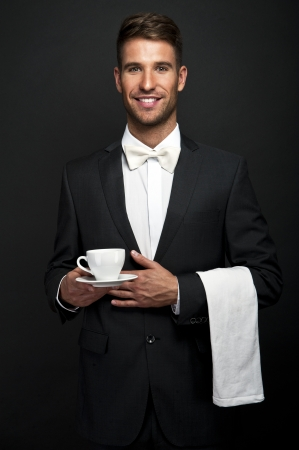 young waiter in uniform serving hot coffee  photo