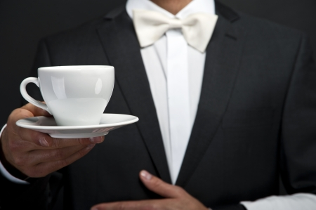 Waiter in suit holding coffee cup photo