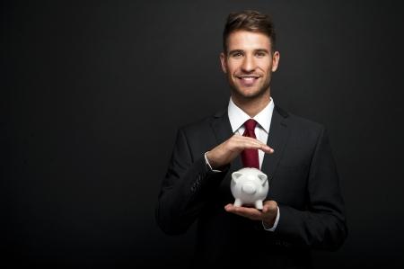 Businessman with piggy bank over dark background Stok Fotoğraf