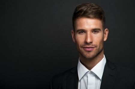 Businessman standing on dark gradient background photo