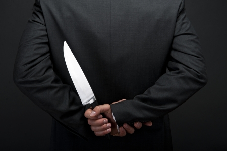 Businessman with knife behind his back Stock Photo