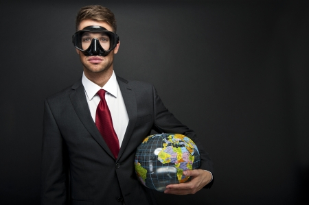 Businessman with world globe and diving mask photo