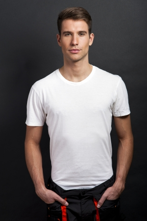 Handsome man posing in white tshirt on dark background in studio. photo