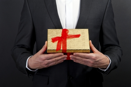 close up of man hands holding gift box over dark background photo