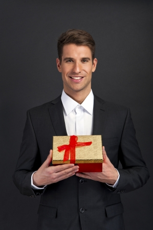 Happy young man carries  present, over dark background photo