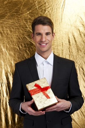 Happy young man carries  present, over gold background photo