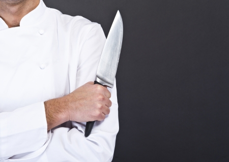 chef knife: Portrait of a young cook man wearing uniform holding a knife over grunge background. Stock Photo
