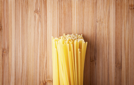 Bundle of Italian spaghetti pasta tied with string lying on old textured wooden boards with a scattering of flour photo