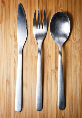 silverware on board wooden background photo