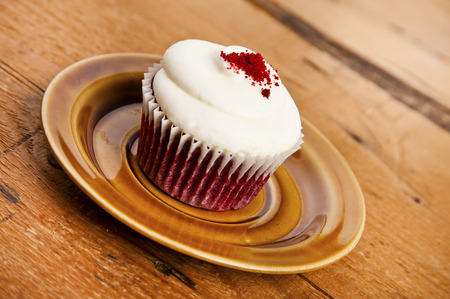 Cupcake on plate over wood background photo