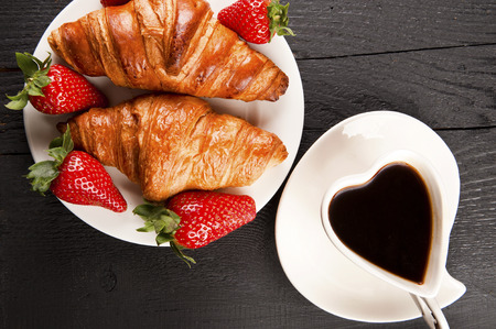 cafe cup in heart shape and croissant with cinamon and anise stars photo