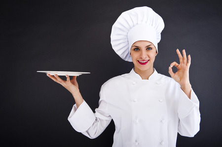 Woman cook or chef serving empty plate and smiling happy photo