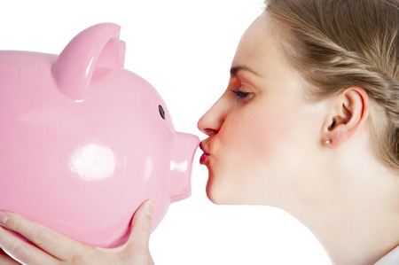 Blond young woman kissing a piggy bank with her lips   photo